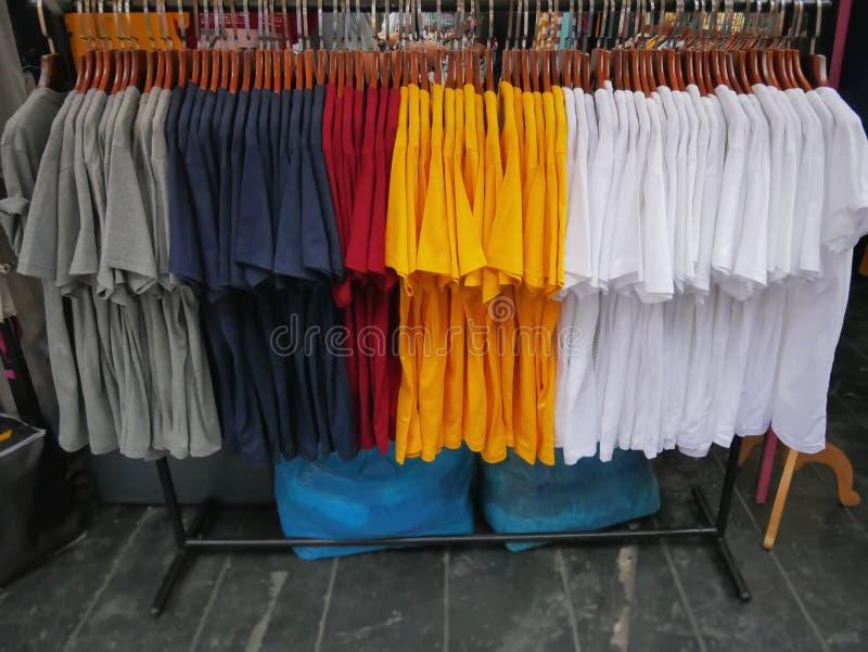 Camisetas coloridas que cuelgan en el estante en la tienda al por menor fotografía de archivo libre de regalías
