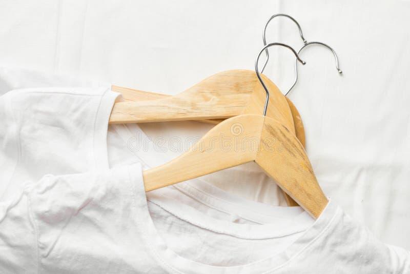 Camisetas de algodón puras blancas en las suspensiones de madera que ponen en el paño de lino Concepto de la venta de los materia foto de archivo