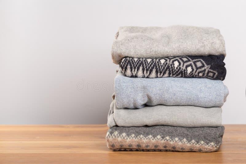 Camisetas diferentes em uma tabela de madeira em um fundo claro Roupa do outono e do inverno fotografia de stock