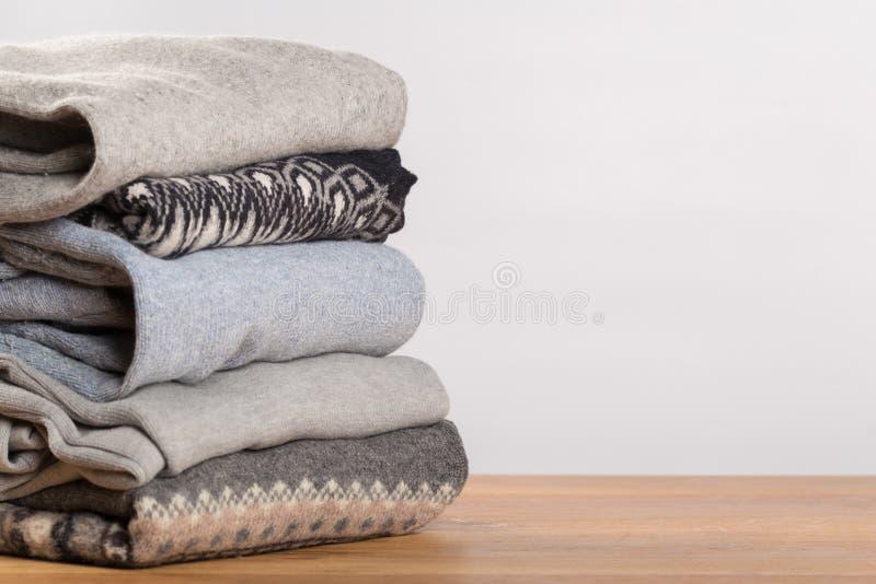 Camisetas diferentes em uma tabela de madeira em um fundo claro Roupa do outono e do inverno fotografia de stock royalty free