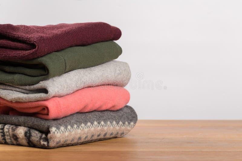 Camisetas diferentes em uma tabela de madeira em um fundo claro Roupa do outono e do inverno fotos de stock royalty free