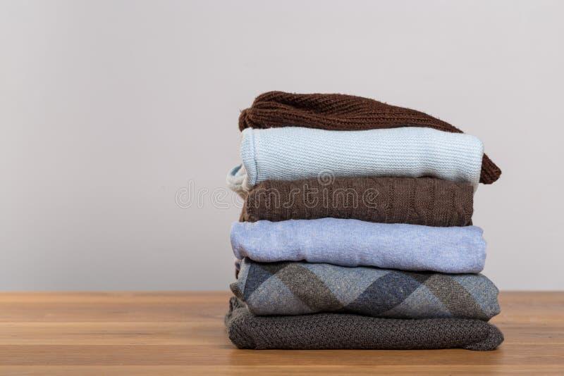 Camisetas diferentes em uma tabela de madeira em um fundo claro Roupa do outono e do inverno imagens de stock