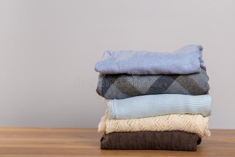 Camisetas diferentes em uma tabela de madeira em um fundo claro Roupa do outono e do inverno imagem de stock