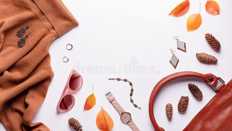 Camisola ou vestuário para mulheres com saco de couro, joias, acessórios de moda e folhas de outono Fundo de moda do outono imagens de stock royalty free