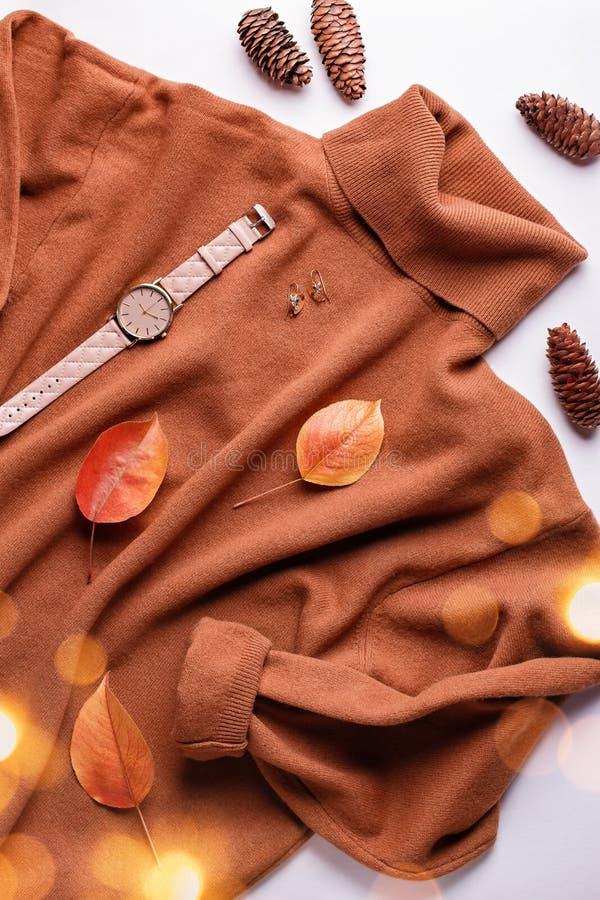 Camisola ou vestuário para mulheres com saco de couro, joias, acessórios de moda e folhas de outono Fundo de moda do outono foto de stock royalty free