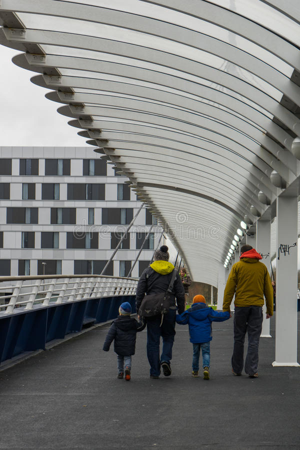 Camminando lungo un ponte che si tiene per mano con i bambini piccoli fotografie stock libere da diritti
