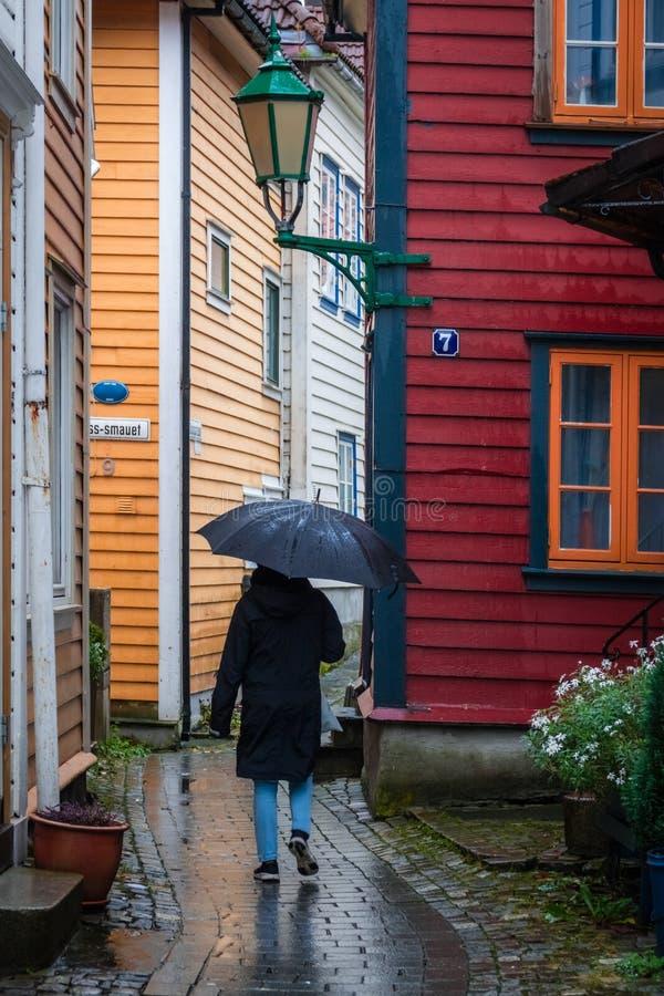 Camminando in pioggia tramite le vie strette nella vecchia città di Bergen fotografie stock