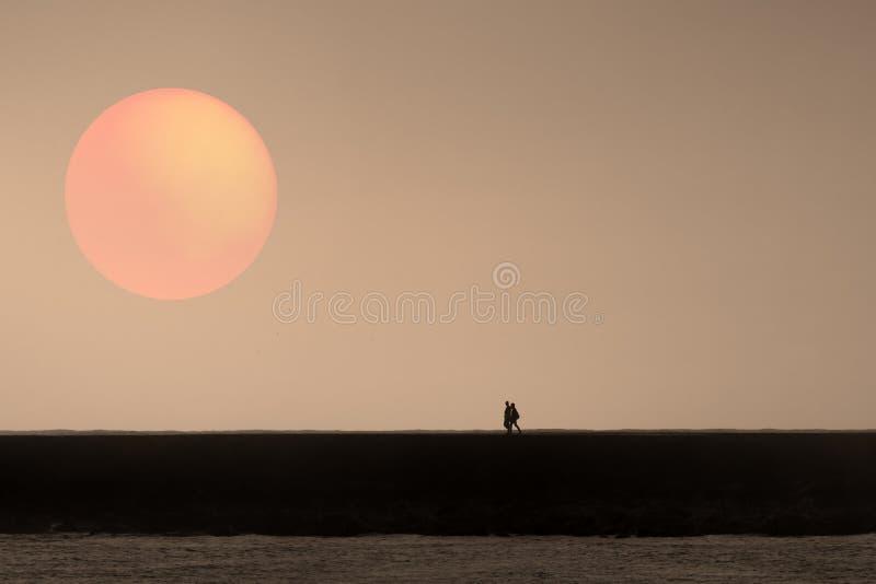 Camminando su un pilastro al tramonto fotografia stock libera da diritti