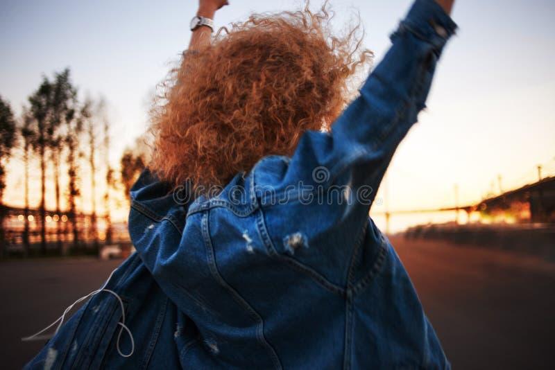 Camminando sulla via, la giovane donna d'avanguardia con capelli fertili va avanti Vista posteriore fotografie stock libere da diritti