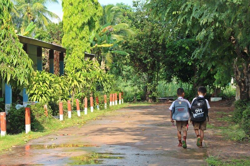 Camminano sulla strada davanti all'edificio scolastico fotografie stock libere da diritti