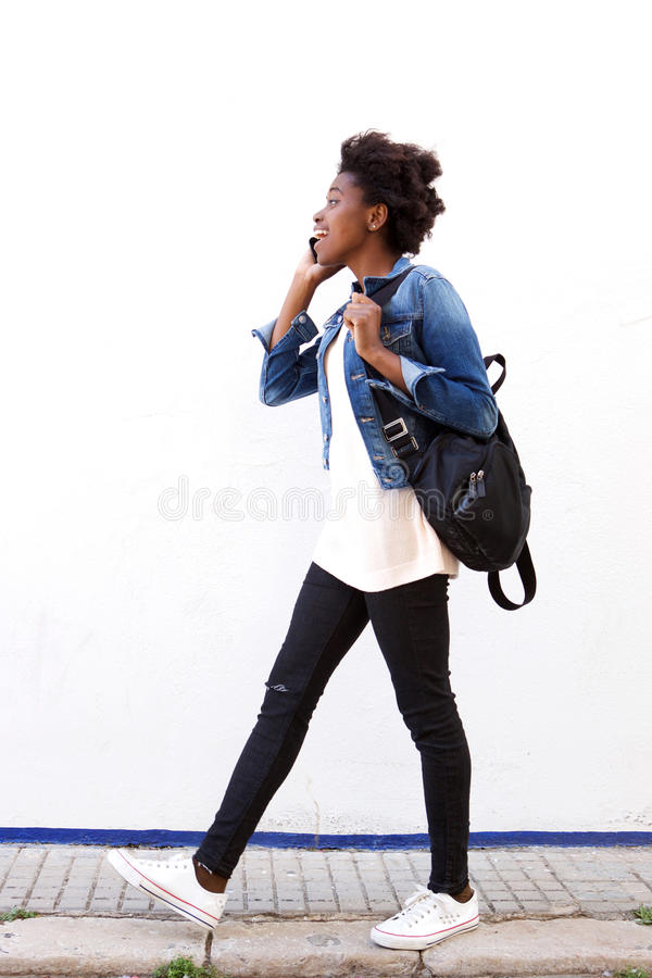 Camminata d'avanguardia della giovane donna esterna e parlare sul telefono cellulare immagine stock
