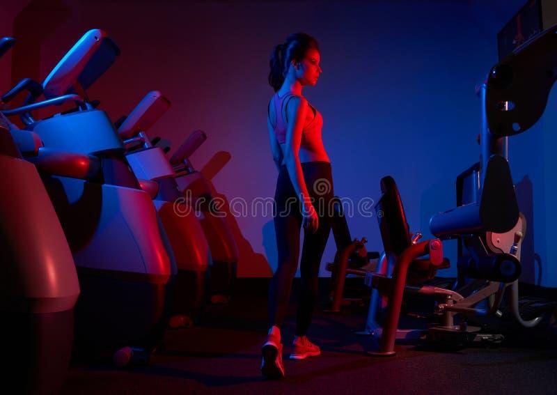 Camminata di modello di forma fisica femminile fra due file del machin di esercizio immagine stock