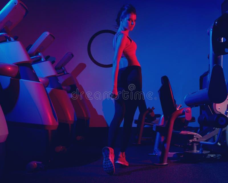 Camminata di modello di forma fisica femminile fra due file del machin di esercizio fotografia stock