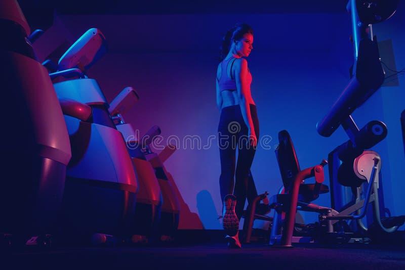 Camminata di modello di forma fisica femminile fra due file del machin di esercizio fotografie stock libere da diritti