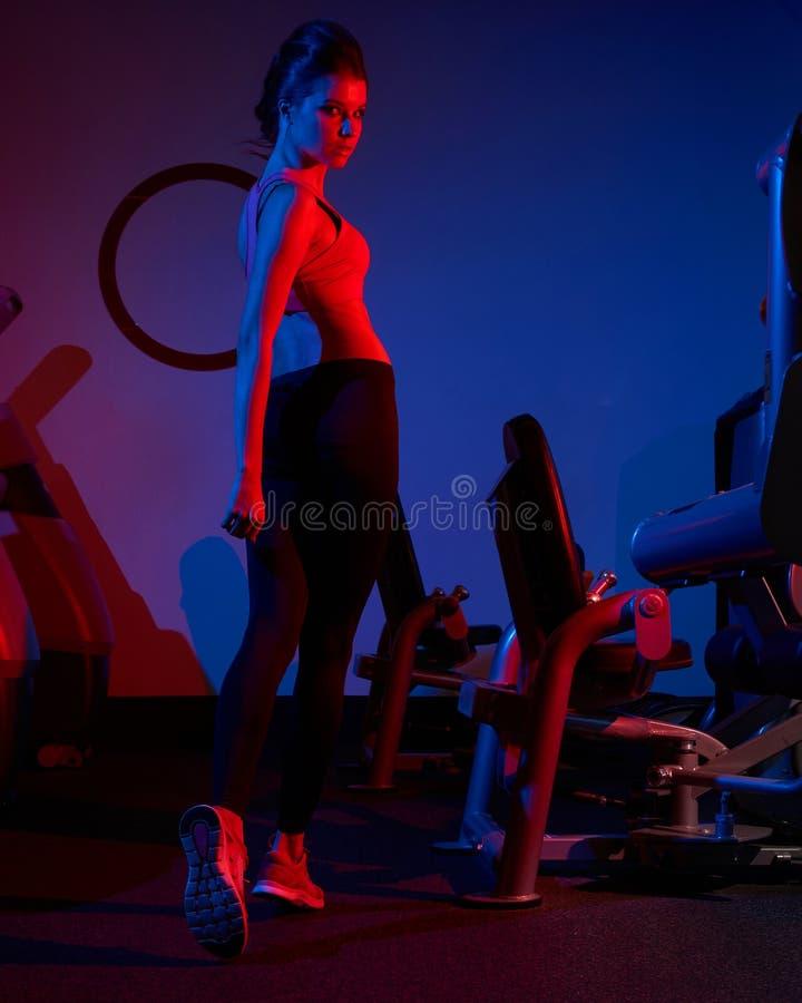 Camminata di modello di forma fisica femminile fra due file del machin di esercizio fotografia stock libera da diritti