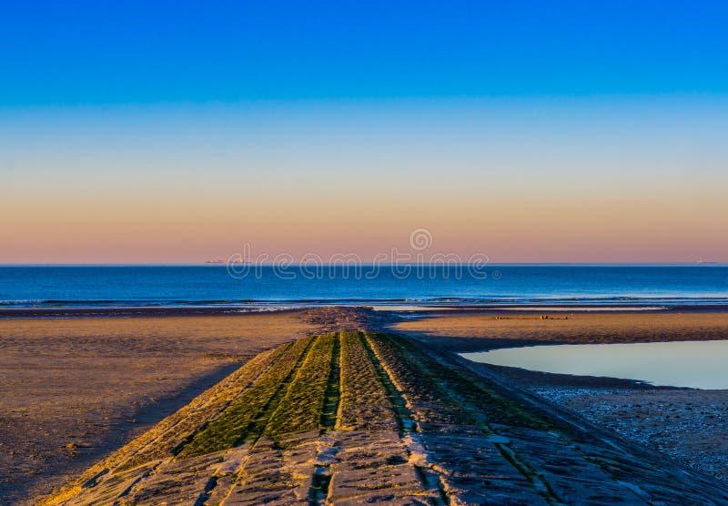Camminata di pietra o rocce che conduce bello e nel cielo variopinto al tramonto, spiaggia di Blankenberge, Belgio dell'oceano, fotografie stock