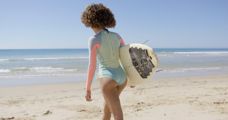 Camminata femminile nel mare da praticare il surfing fotografia stock libera da diritti