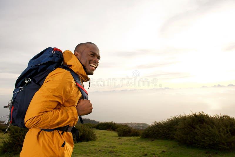 Camminata maschio afroamericana felice di viaggiatore con zaino e sacco a pelo all'aperto in natura fotografia stock