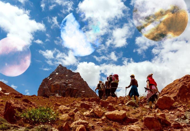 Camminata straniera del paesaggio e delle viandanti della montagna del pianeta fotografia stock libera da diritti