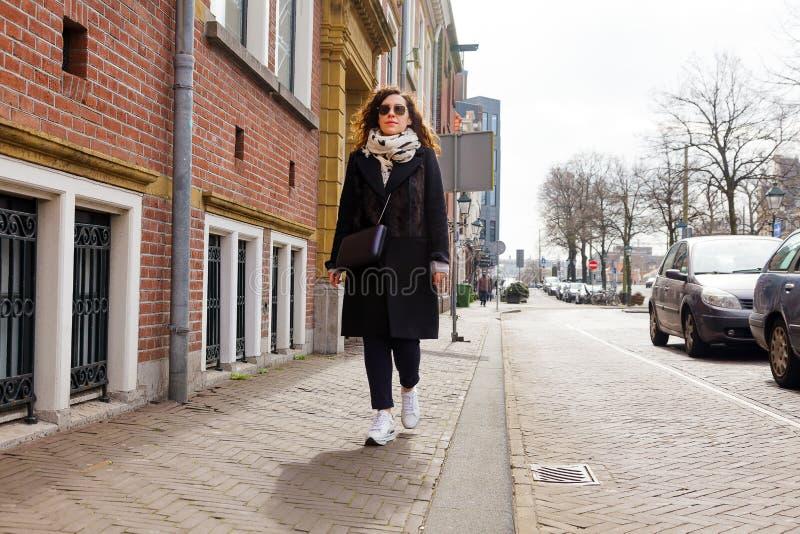 Camminata turistica di modo della giovane donna del ritratto della città della via della ragazza del cappotto di vetro della moll fotografie stock