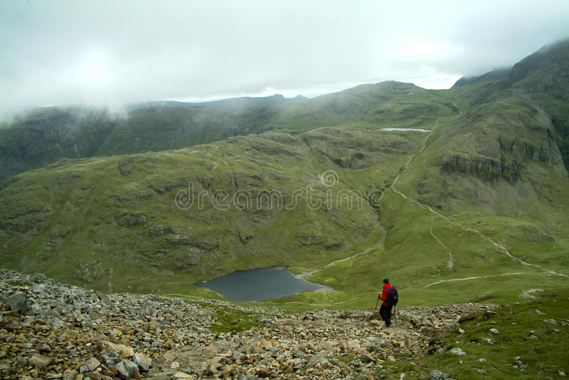 Camminatore solo che discende dal grande timpano a Styhead il Tarn fotografia stock