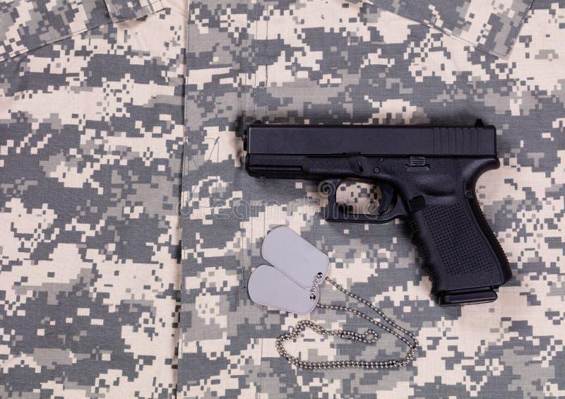 Cammuffi l'uniforme di vestito da battaglia con le etichette e la pistola di identificazione immagine stock