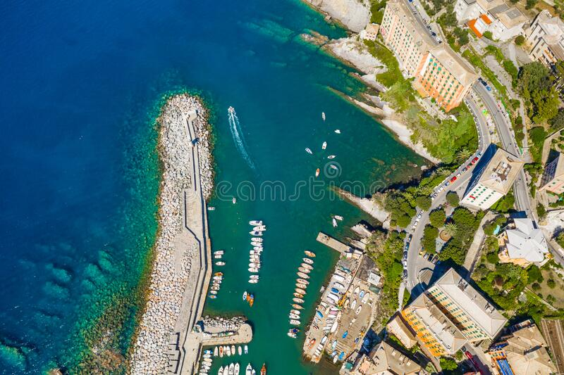 Camogli Harbor aerial view. Colorful buildings, boats and yachts moored in marina with green water royalty free stock images