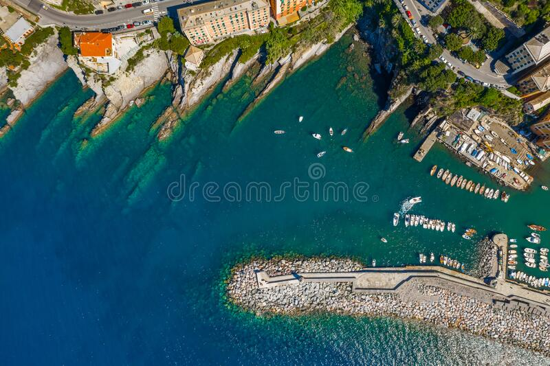 Camogli Harbor aerial view. Colorful buildings, boats and yachts moored in marina with green water. royalty free stock photography