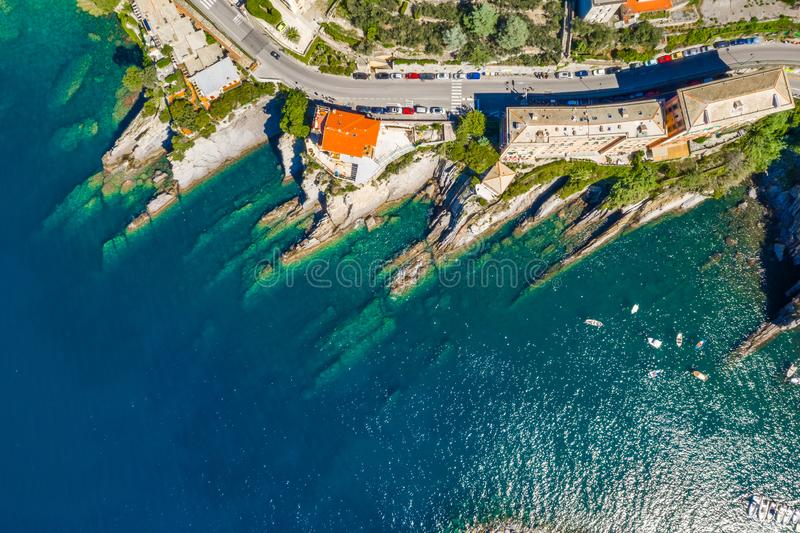 Camogli rocky coast aerial view. Boats and yachts moored near harbor with green water stock images