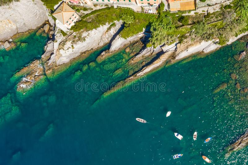 Camogli rocky coast aerial view. Boats and yachts moored near harbor with green water. stock image