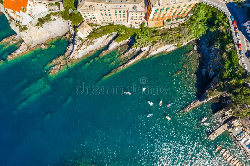 Camogli rocky coast aerial view. Boats and yachts moored near harbor with green water. stock images