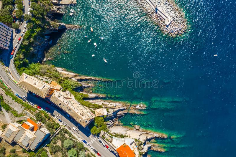 Camogli rocky coast aerial view. Boats and yachts moored near harbor with green water and lighthouse. stock image