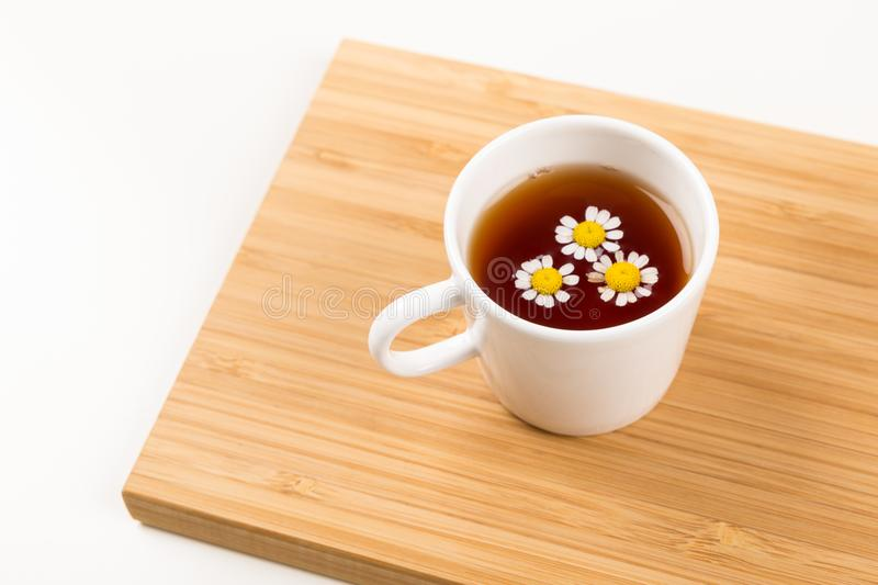 Camomile Tea, Good Morning, Cup of tea with flowers. Camomile Tea, Good Morning, Cup of tea with flower in it on a wooden tray stock photography