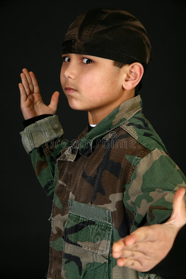 Camouflage Boy. Attractive 9 year old Filipino boy in camouflague fatigues doing martial arts stock photography