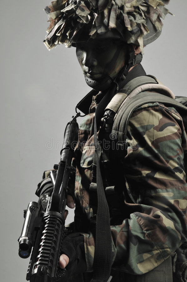Camouflage soldier fully equipped stock photo