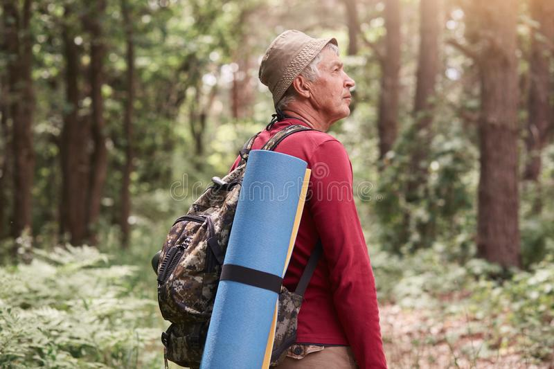 Camp, adventure, traveling, active recreation concept. Outdoor photo of eldery man with backpack and rug, wearing red sweater and royalty free stock photos