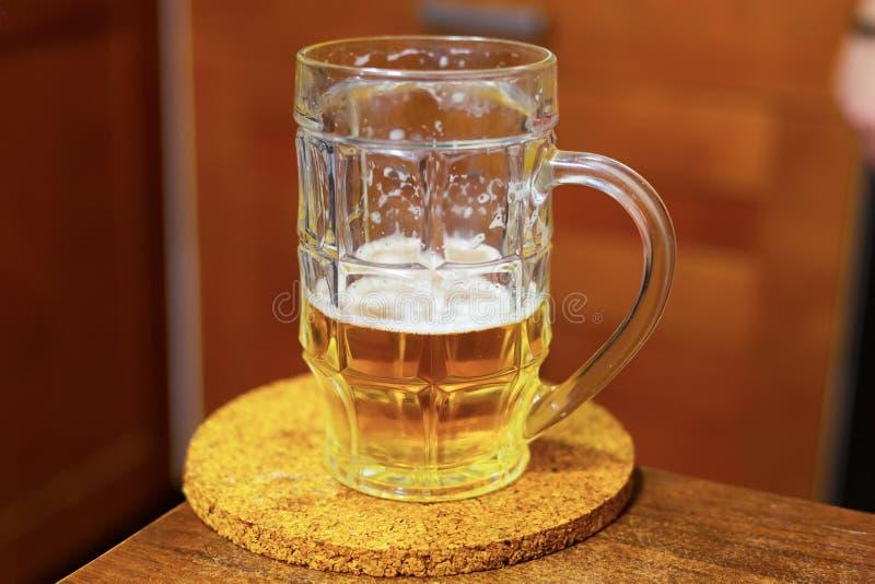 Camp d'or de bière de tasse sur une table en bois sur un bar brouillé de conception de fond À moitié une tasse de bière photo stock