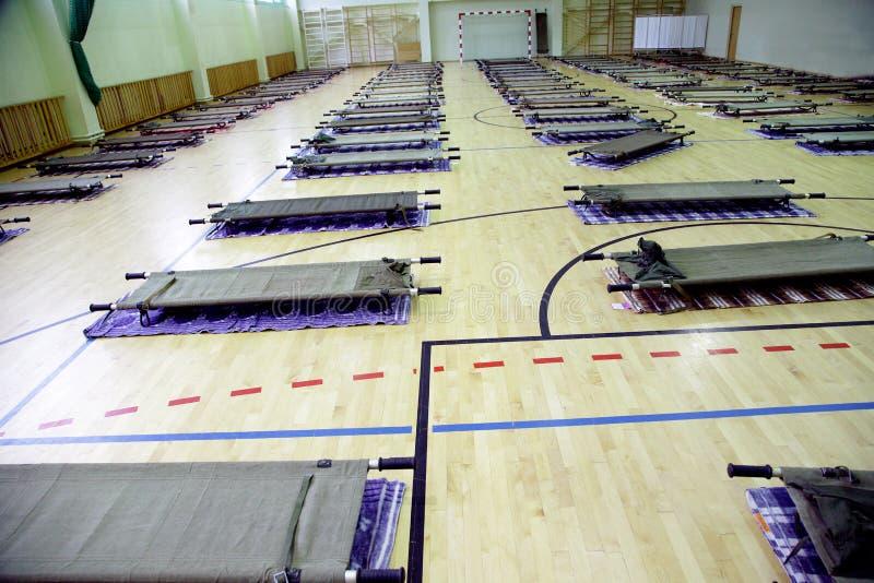 Camp de réfugié dans la salle de gymnastique d'école complètement avec des stretcers photo stock