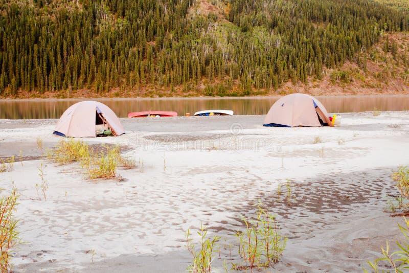 Camp de tente de canoë au fleuve de Yukon dans la région sauvage de taiga image libre de droits