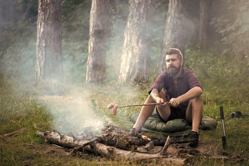 Camp de vacances Saucisses de rôti de voyageur d'homme sur le bâton sur le feu de camp dans la forêt images libres de droits