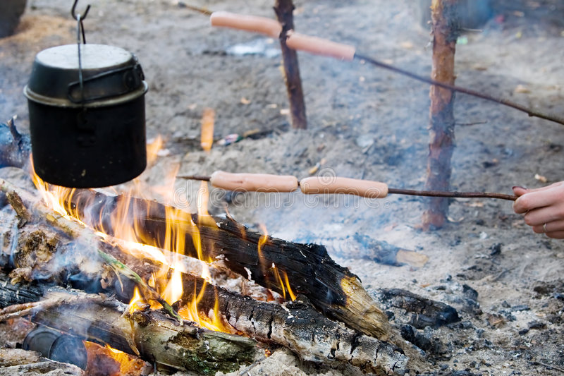Camp-fire. With pot on it and hands roast the sausages royalty free stock photography