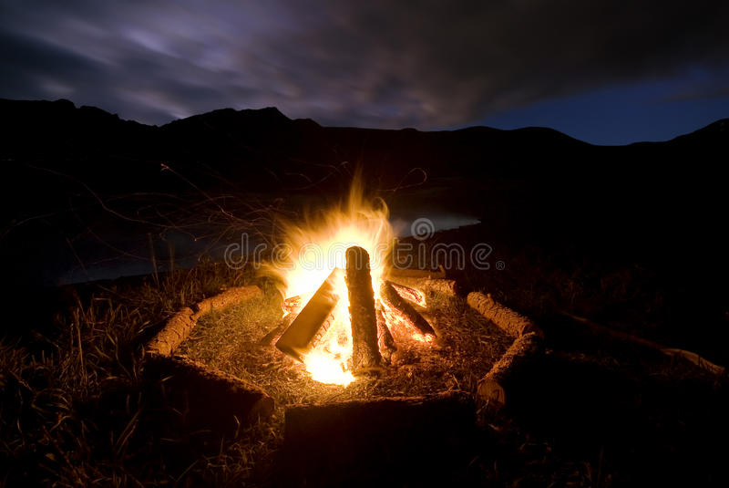 Camp fire beside lake and mountains. Camp fire with logs arranged around fire beside lake and mountains, New Zealand royalty free stock photo