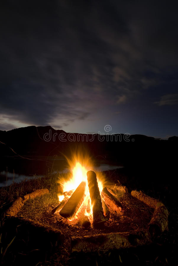 Camp fire beside lake and mountains. Camp fire with logs arranged around fire beside lake and mountains, New Zealand royalty free stock images