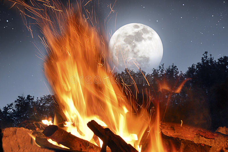 Camp fire in the moonlight. A fires burns inside the forest in a full moon night