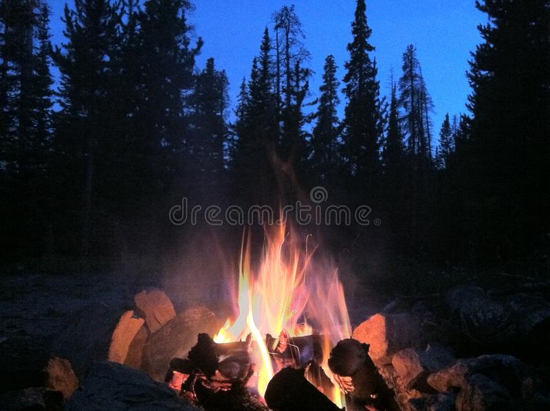 Camp fire at twilight stock images
