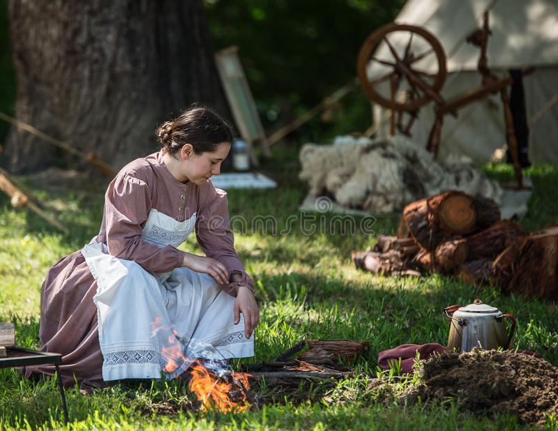Camp Follower. A young woman sets a fire for cooking at a Civil War era camp in northern California royalty free stock image