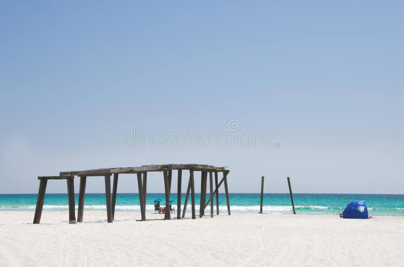 Camp Helen State Park Pier in Panama City Beach Florida. There are unrecognizable people relaxing in two beach chairs. There is also a beach tent set up in the stock photography