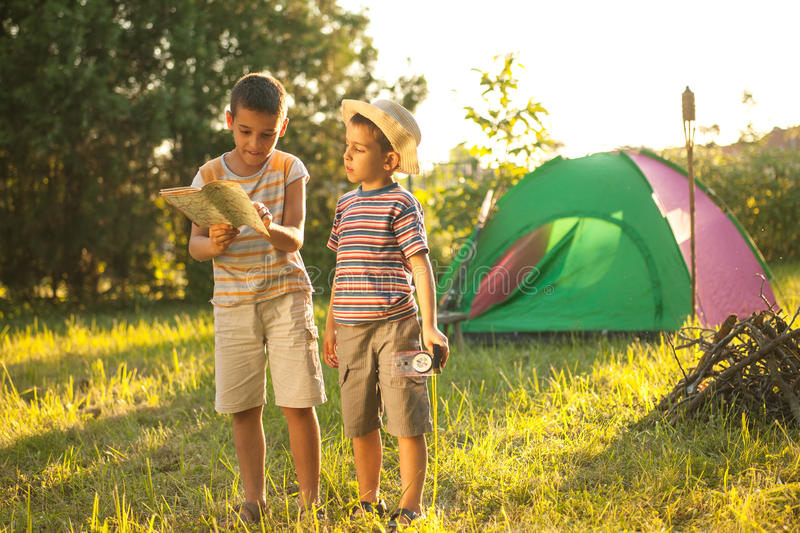 Camp in the tent - two brothers on the camping. Two boys on a camping trip, learning how to read a compass stock photos