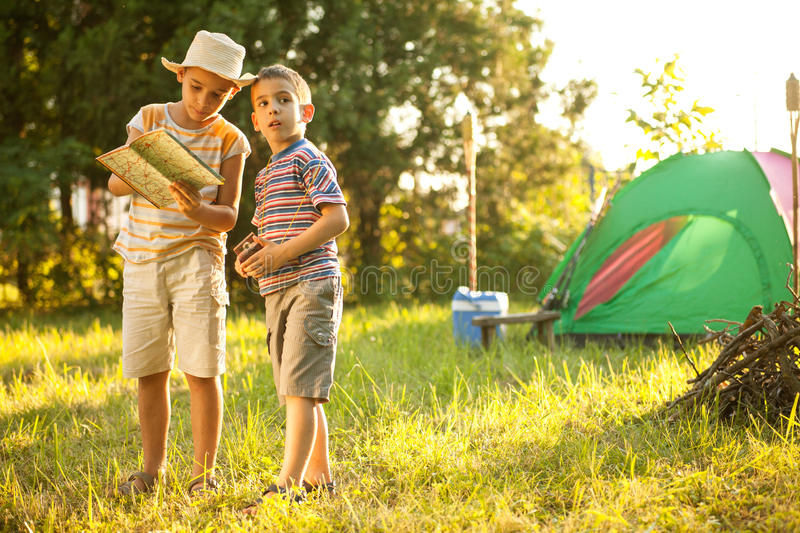 Camp in the tent - two brothers on the camping. Two brothers on the camping looking at map royalty free stock images