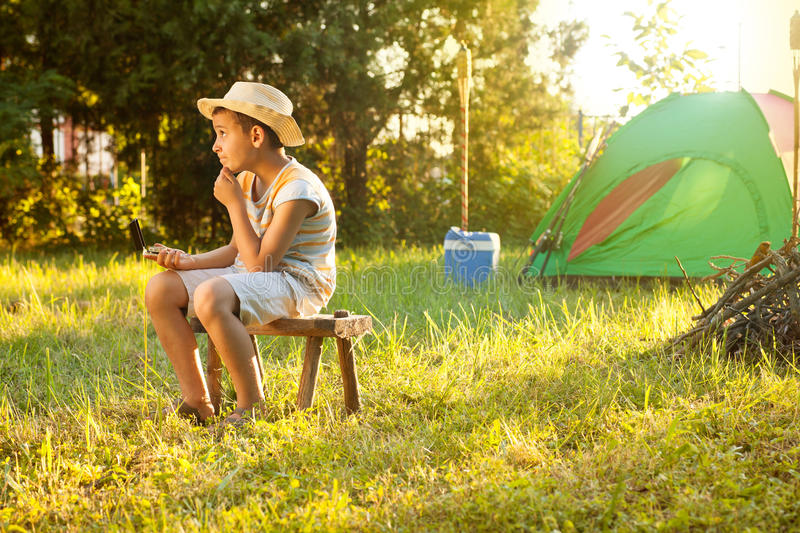 Camp in the tent - young boy on a camping. Young boy on capping, learn how to read a compass royalty free stock photography